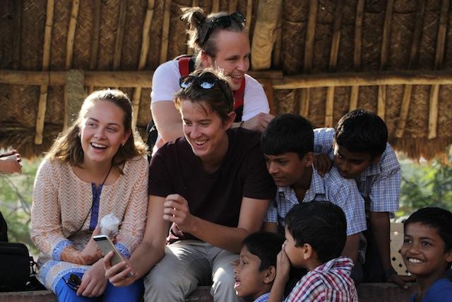 Urte, Andreas og Nils viser fram bilder til elever på Dreamschool.